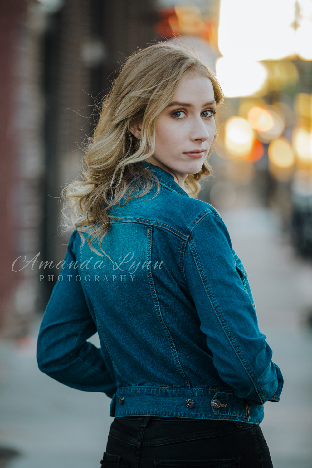 High school senior girl looking over her shoulder with beautiful Tulsa, Oklahoma sunset behind her by Amanda Lynn Photography.
