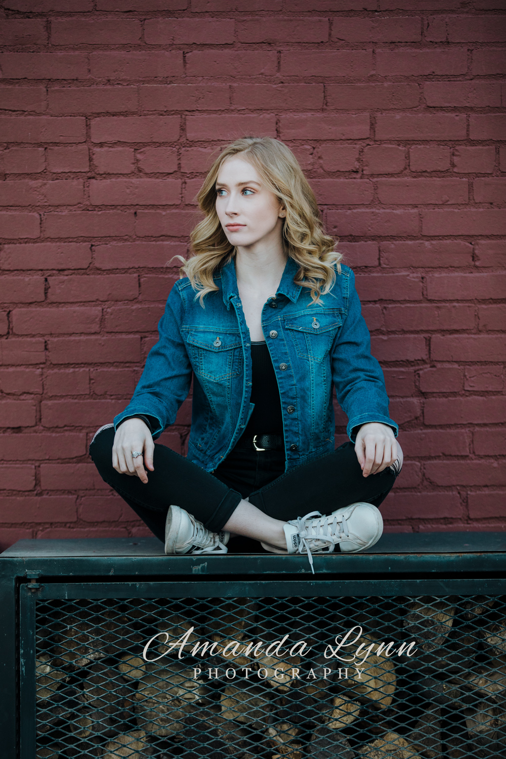 Oklahoma senior girl wearing casual clothing, sitting on top of a firewood bin in downtown Tulsa, Oklahoma by Amanda Lynn.