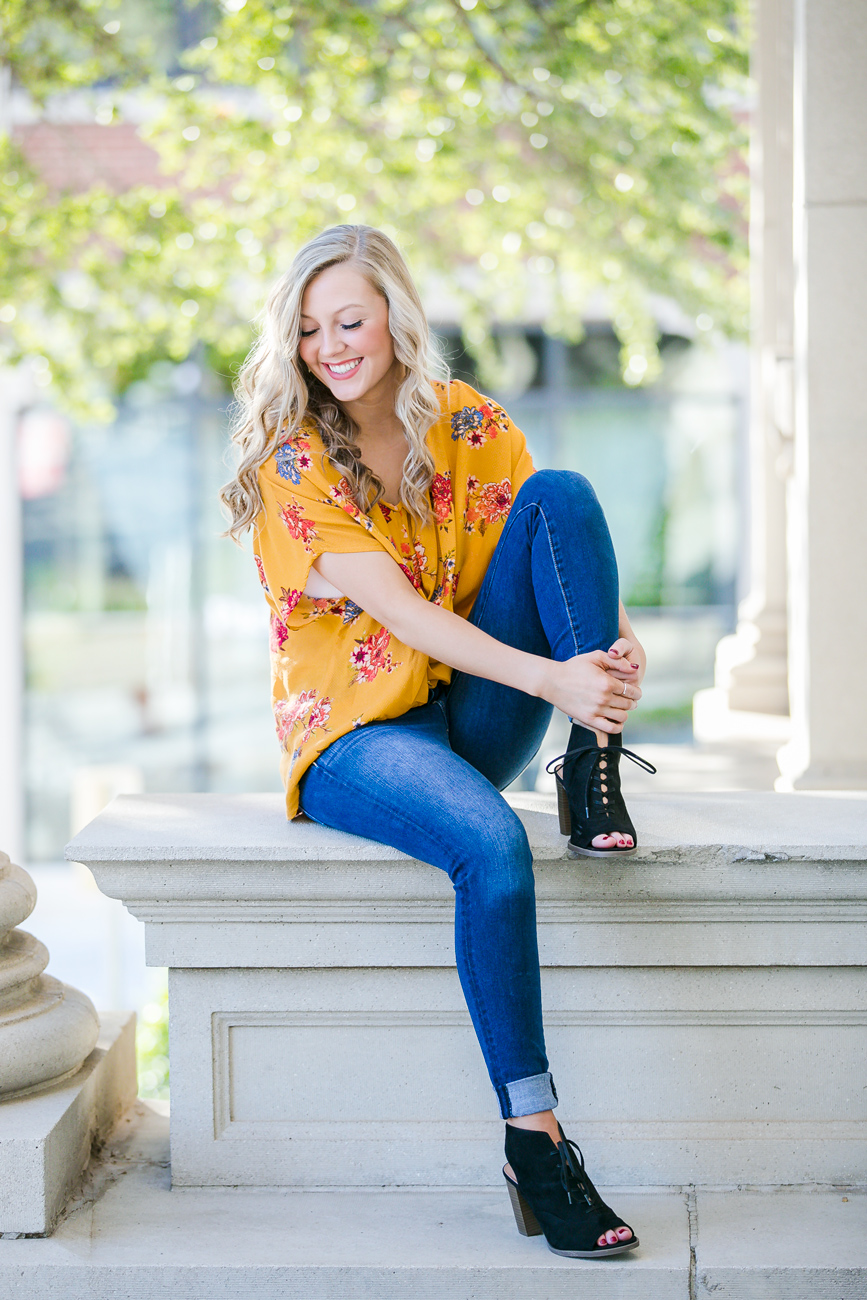 Senior girl with long blonde hair, wearing blue jeans, heels, and yellow summer shirt, sitting on concrete pilar in automobile alley in Oklahoma City.