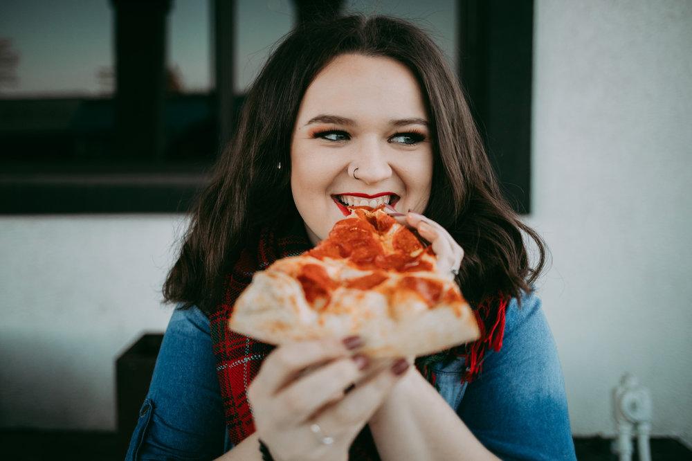 Oklahoma senior girl eating a slice of pizza in the Plaza District in OKC.