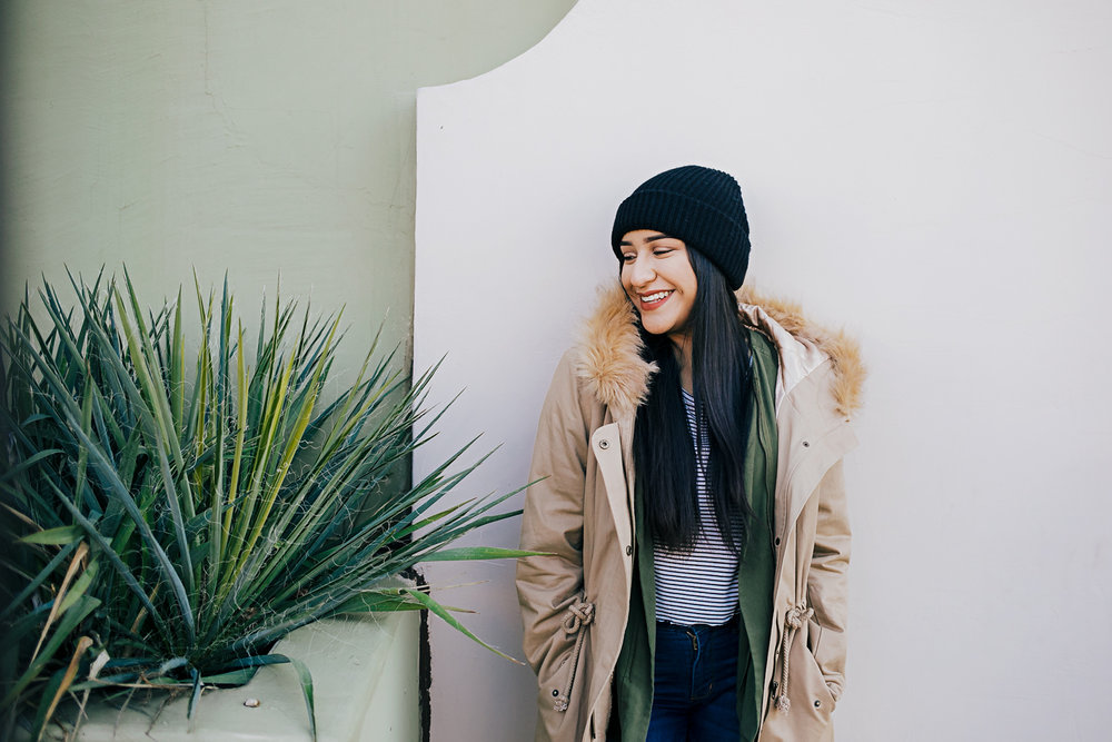 Oklahoma high school senior girl with long dark hair, wearing a heavy coat and black hat, leaning against the wall in the Paseo District in Oklahoma City.