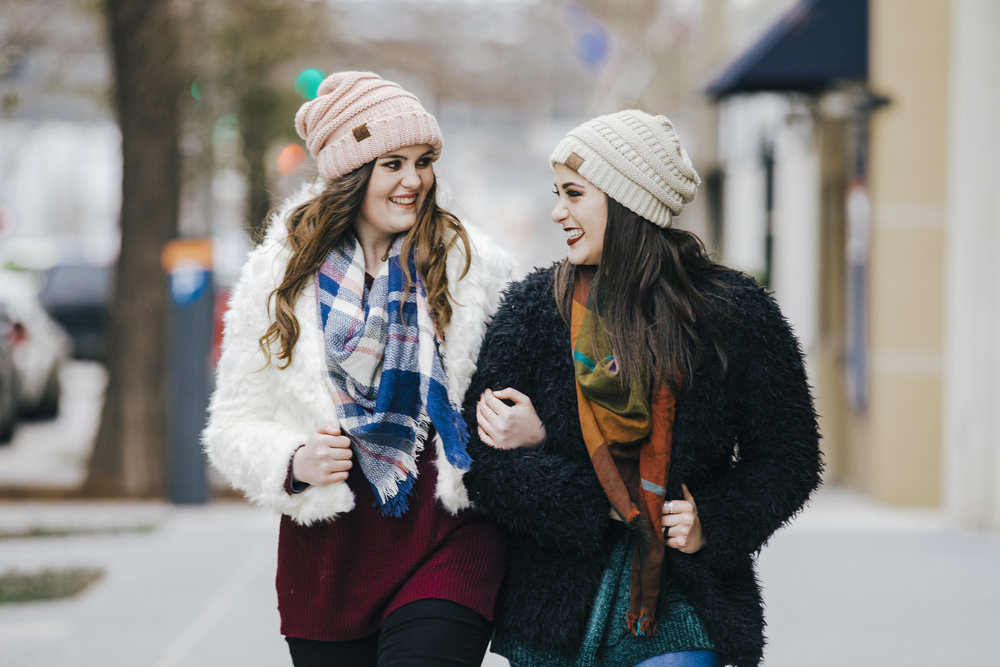 Two senior girls dressed in wither clothing, walking with locked arms in downtown Oklahoma City.
