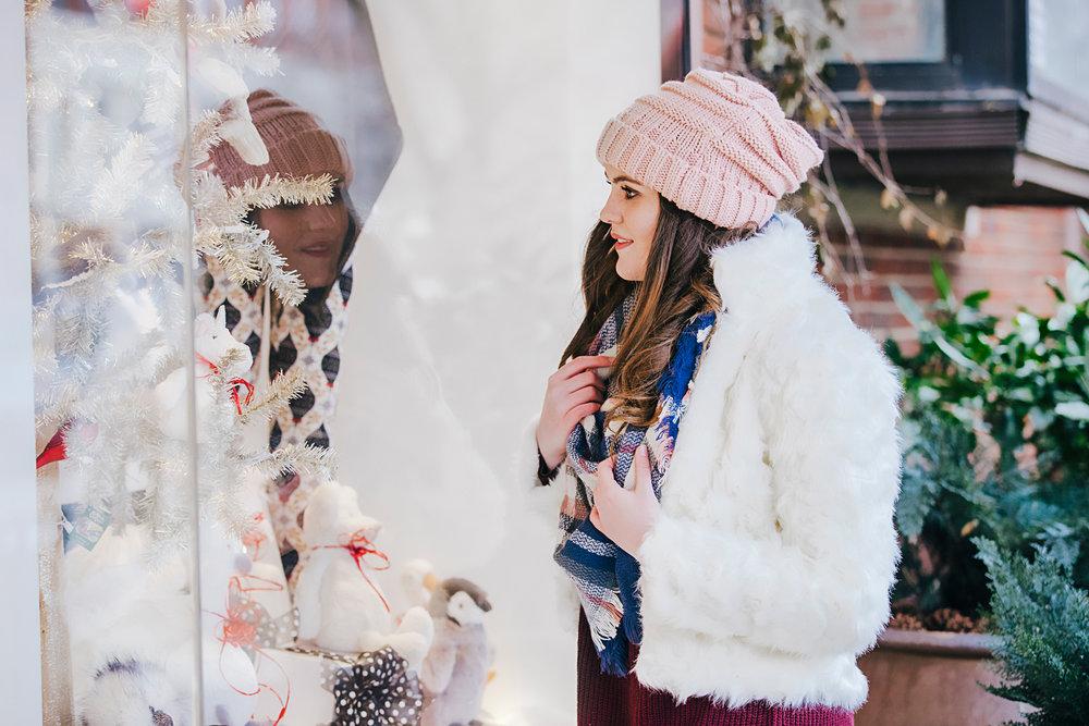 High school senior girl wearing white winter jacket and pink hat, window shopping in Bricktown in OKC.