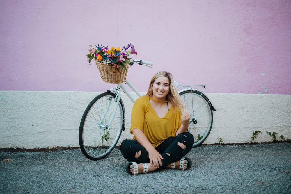 High school senior girl wearing black jeans and yellow top, sitting on ground in front of a bike with flowers in the basket in the Paseo District of Oklahoma City by Amanda Lynn.