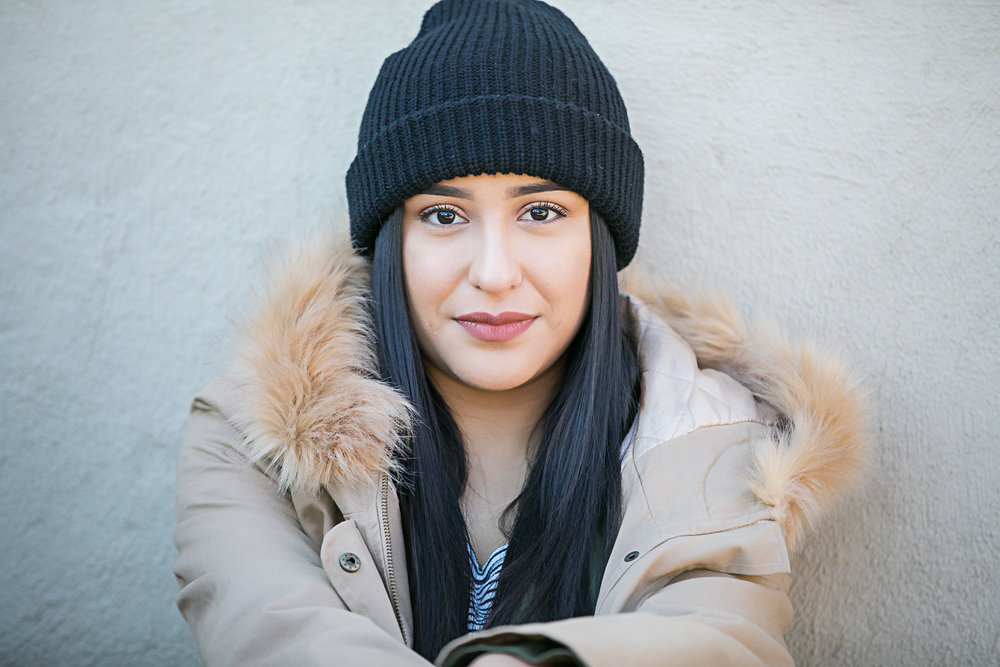 Senior girl wearing black beanie and brown furry coat, sitting against a white wall in the Paseo District in Oklahoma City, by Amanda Lynn Photography.