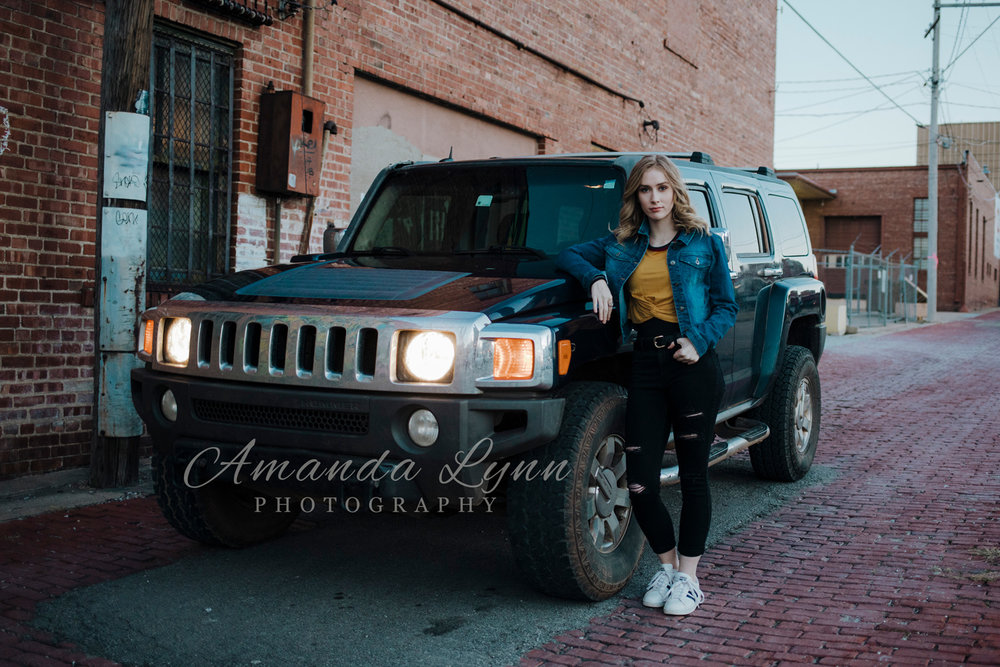 High school senior girl wearing casual clothing leaning against her Hummer H3 in downtown Tulsa, OK.