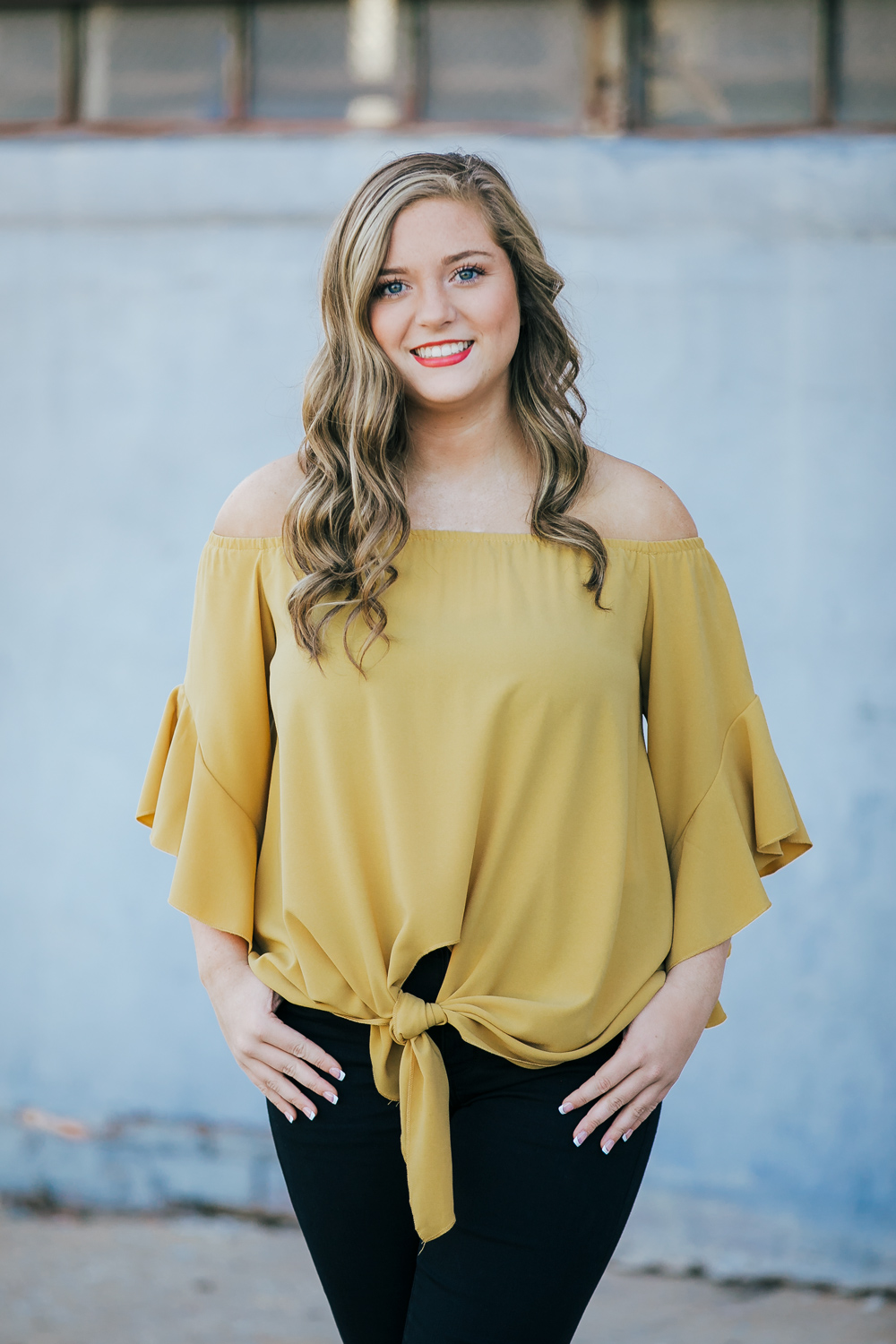 High school senior girl with long blonde hair wearing yellow top and black pants standing in front of a blue wall in automobile alley in OKC.
