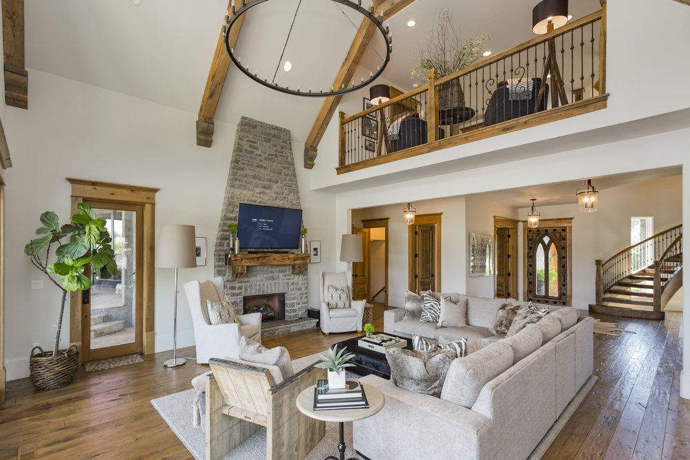 Gas fireplace with stone mantle, vaulted ceilings, and wood beams overlook the outdoor pool and entertainment area.