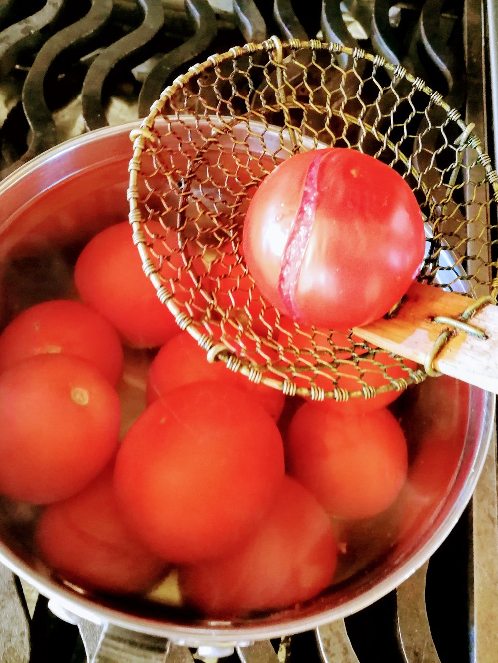 Blanching Tomatoes - When the skin begins to crack, remove the tomatoes from the boiling water and place them in a bowl of ice water.