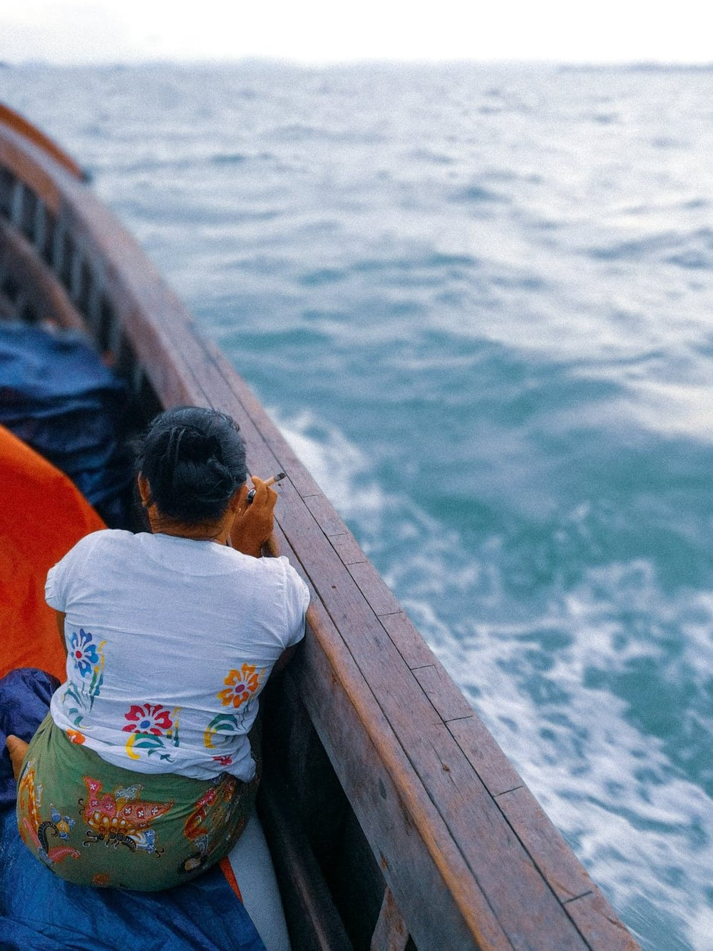 On a boat from Myeik City going to a remote island (Dome Island) in Myanmar's Mergui Archipelago. The woman in this photo is smoking cheroot cigar which are widely popular in Burma and India.