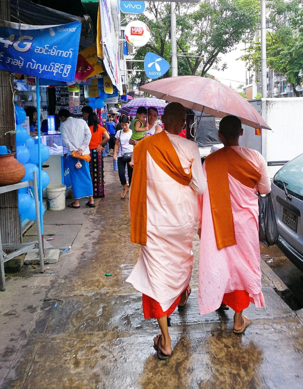 Two Buddhist nuns avoiding the rain in Yangon.