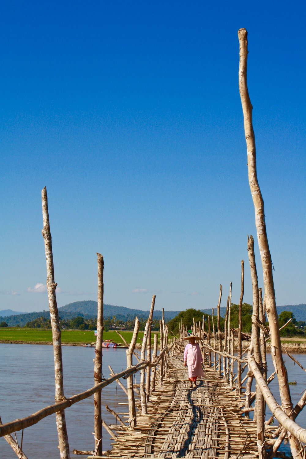 a Buddhist nun crossing a bridge in Myanmar