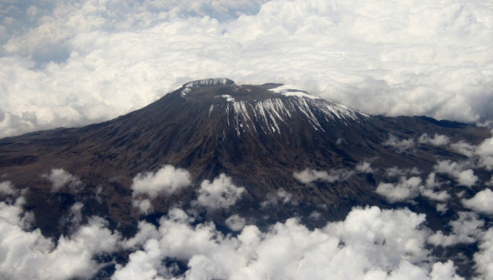 Aerial photo of Mount Kilimanjaro during the summer. Climbing mount Kili responsibly means you will need to follow these rules. Book with an ethical tour company that doesn't exploit porters or risk their lives. Read The Uprooted Rose travel blog for more.