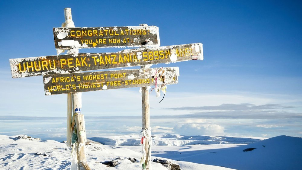 The view from the top of Mount Kilimanjaro after a long climb. Every year, thousands of climbers scale up Africa's highest point stands at 5,895 meters tall. Learn more about planning your trip to Tanzania Responsibly with FairVoyage.com