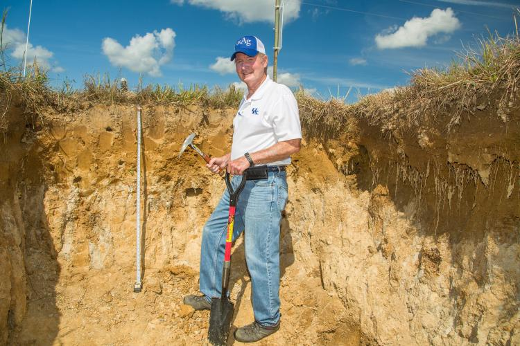 UK soil scientist Lloyd Murdock shows the fragipan layer in the soil in a pit at the UK Research and Education Center farm in Princeton. Photo by Stephen Patton, UK agricultural communications.