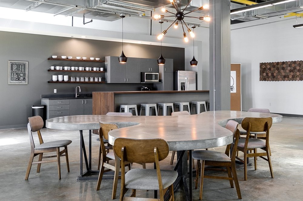 The spacious kitchen included welcoming lighting and comfortable seating, encouraging employees to linger for meaningful periods of engagement, facilitating informal employee interactions and connections across teams. -