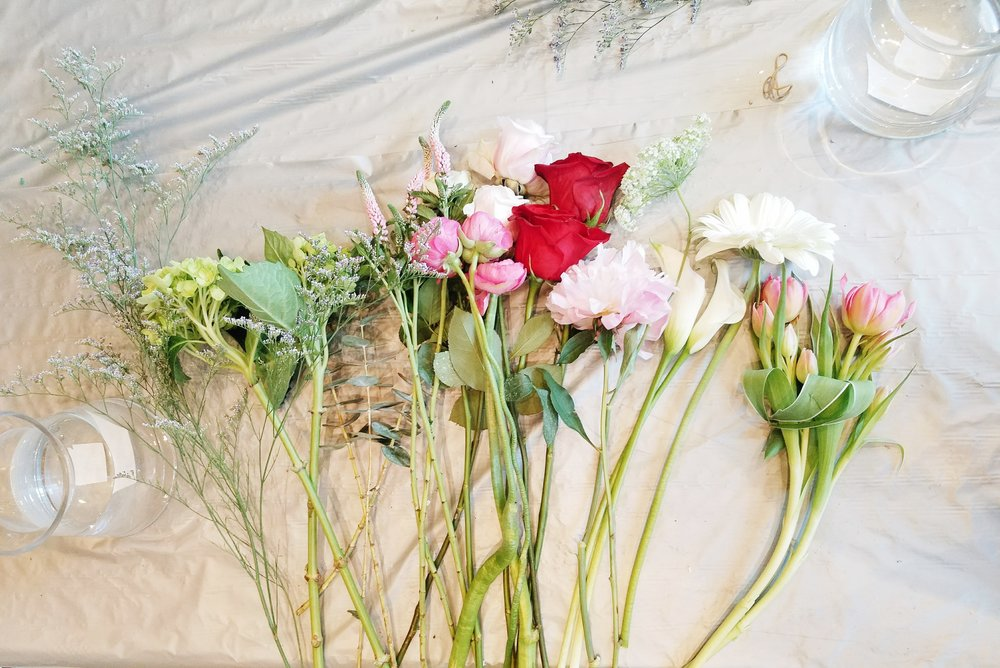 Left to Right: Limonium, hydrangeas, celosia, ranunculus, white roses, red roses, peony, calla lilies, bouvardia, gerber daisy, and tulips.