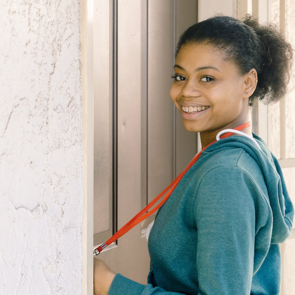 Teen from First Place For Youth opening door