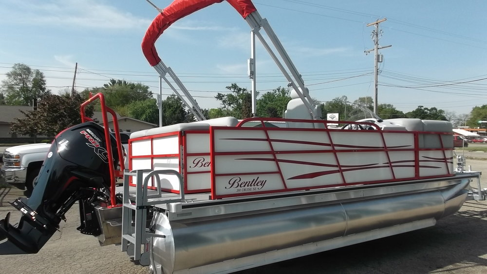 Rear boarding ladder and bimini top are standard. This boat also has an optional red powder coated ski tow bar