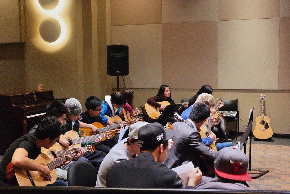 多元化的学生在大学课堂学习乐器中进行岩石教会服务