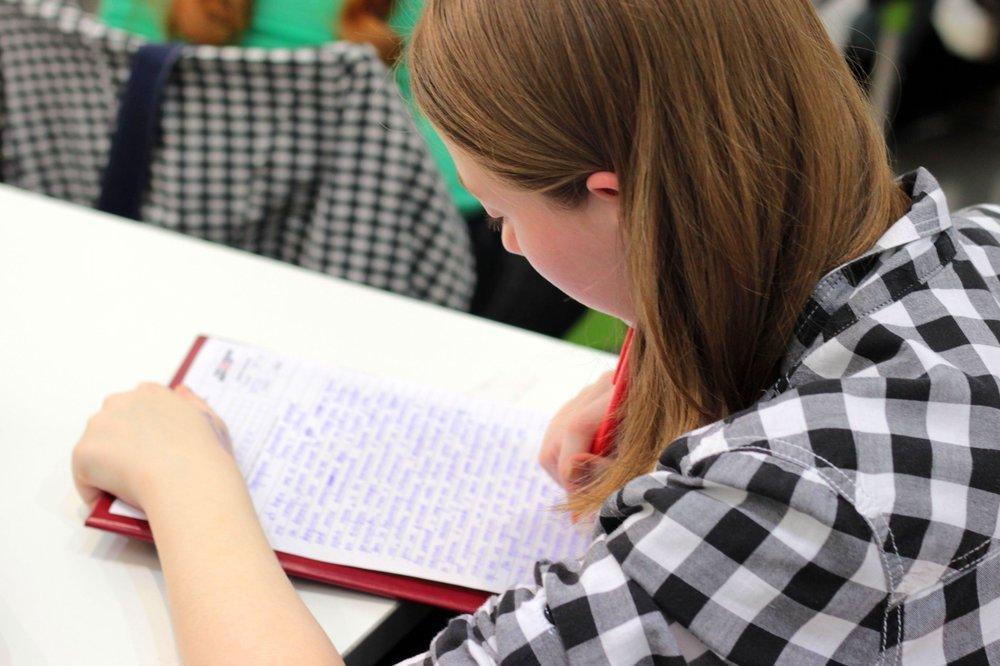 Giovane donna durante un'accademia di leadership rock, prendere appunti e studiare