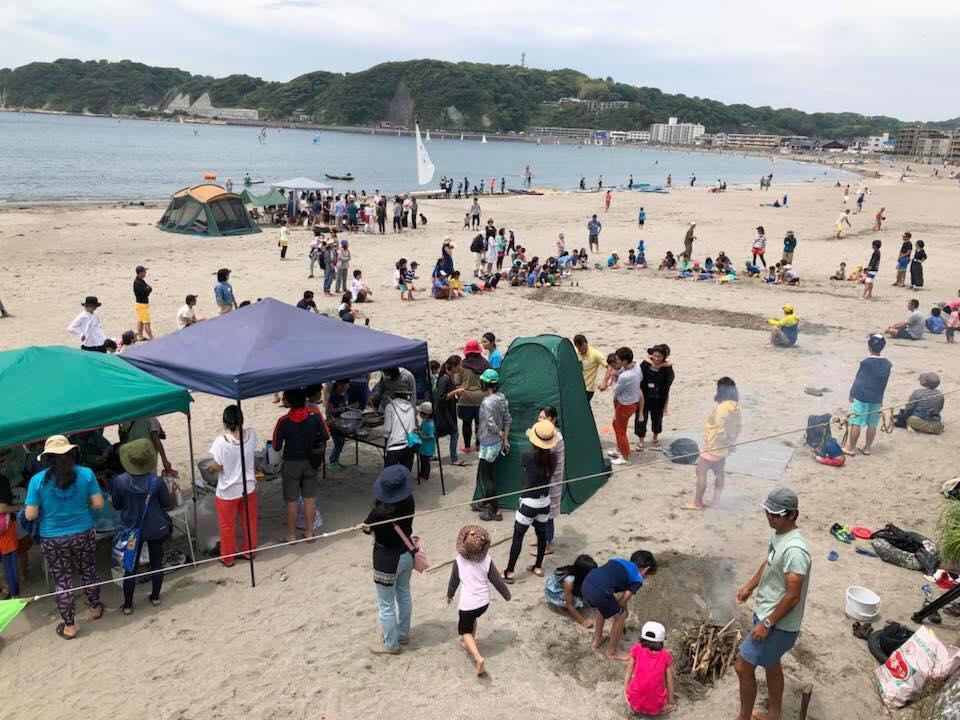 テント下では収穫してきた材料が次々に調理され、浜では子どもも大人も白熱のビーチフラッグ大会。手前の焚き火では、海藻で巻いた立派な肉も蒸し焼きにされています... 逗子だけど、ポリネシア風!