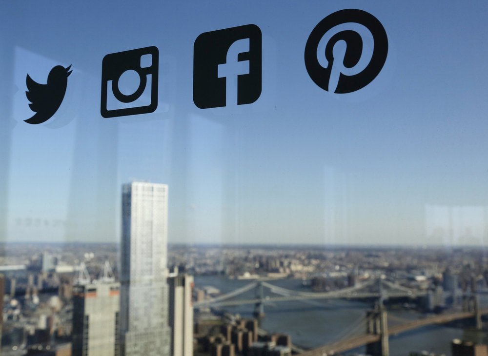 Icons for Twitter, Instagram, Facebook and Pinterest are displayed on a window in New York. Nearly half of U.S. households carry credit card debt, which means many of the friends making you jealous on Instagram may not be able to afford the vacations they post about.