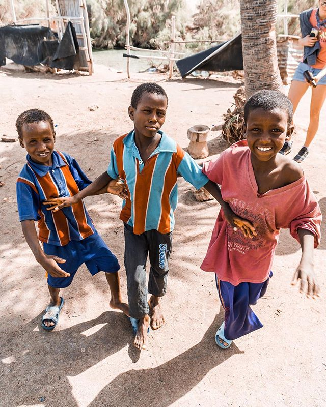 Local eyes... 🇪🇹 - We met these little guys whilst swimming on Lake Afrera and huge salt lake in northern Ethiopia.  At first they were shy, nervously shuffling about and hiding behind a near by palm tree. They were intrigued by us and our cameras but didn't quite have the confidence to approach.  After a while the bravest one (middle) came over and signalled that he wanted to hold our cameras. After a few minutes of showing him how it worked his mates came over and they all started dancing around, posing for the camera like natural born showmen! After each and every click they asked to see the picture, gathering round the screen with huge grins on their faces to observe their work.  Sometimes there's nothing better than a camera to spark a conversation.  Tipped by @hazelfairall  Points if you spotted Jess doing her bit to keep Ethiopia tidy in the background 😅 - #localeyes