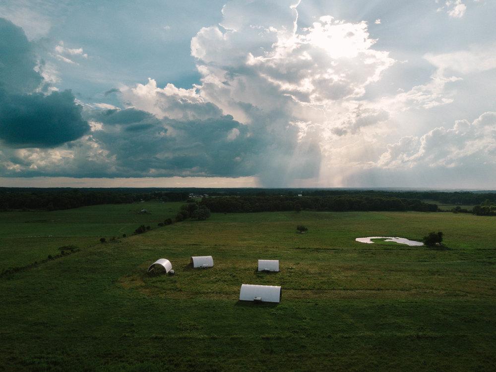 Chicken hoop houses under magnificent sky.