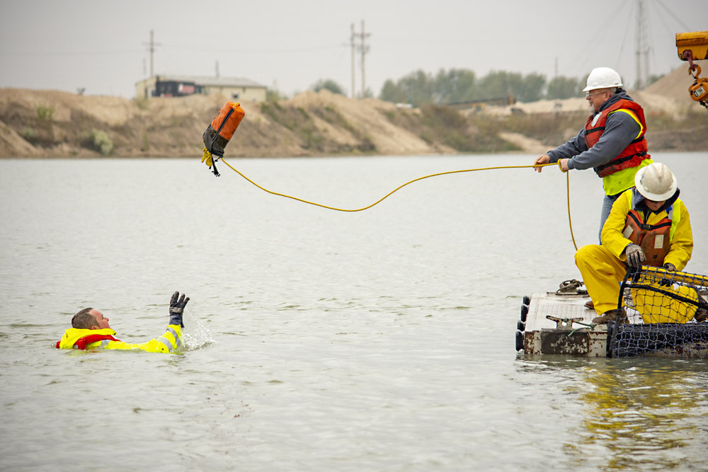 Photos by BRADY JONES/Lyman-Richey Corporation   Employees from Lyman-Richey Sand & Gravel and Central Sand and Gravel pull Field Safety Specialist Peyton Connelly out of the water as part of their hands-on water safety training course held at LRSG's Valley, Neb., location.