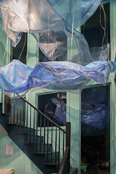 """Ocean Currents""  Created by students in Kimberly Collins Jermain's ""Site Specific - Artwork from Proposal to Installation"" course at Endicott College. This installation was designed to transform a restaurant vestibule waiting area located at the bottom of a two-story stairwell into an underwater realm.  Materials: Fabric, Wire, Aluminum, Window Mesh"