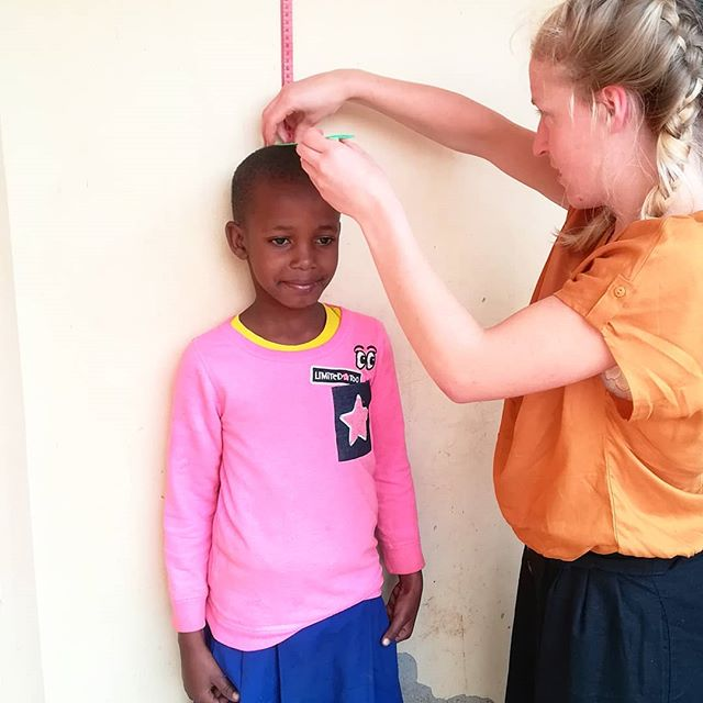 We have medical students with us this month doing their medical elective. Today they started a nutrition needs test analysis in the school to help us implement a year long nutrition programme. Here's Faith measuring the height of one of the girls from standard 2 🙏 . #healthamplifier #healthcare #nutrition #medics #medicalelective #tanzania #kikavu #primaryschool