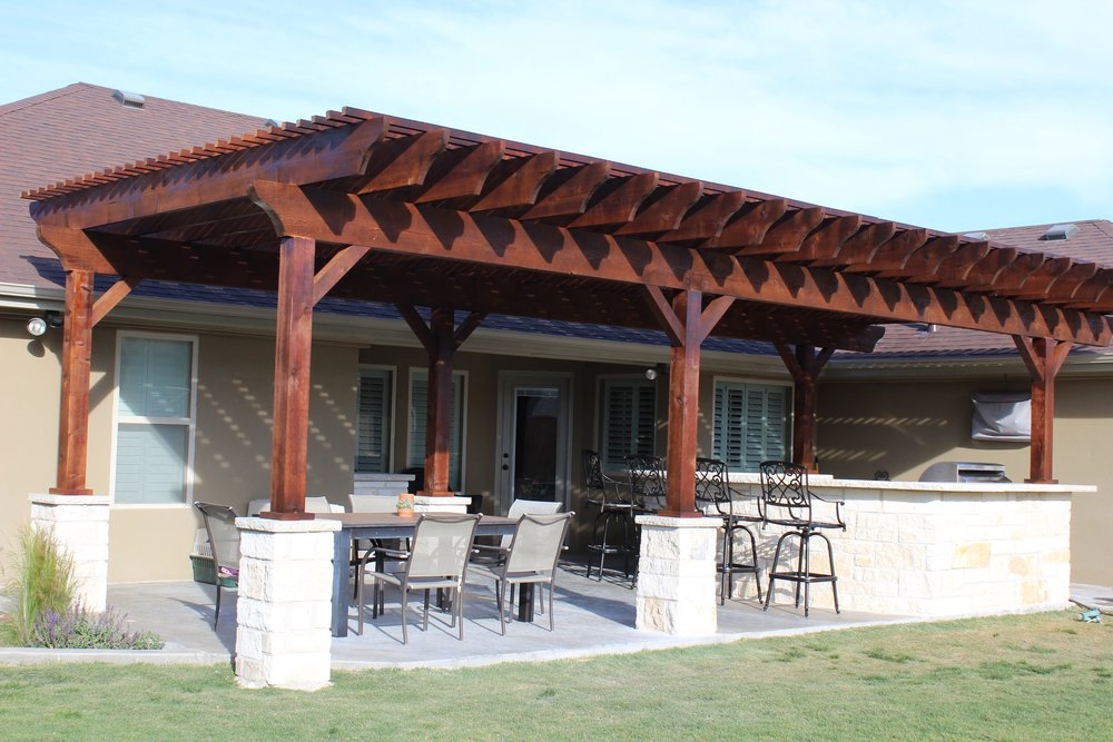 FEATURED PROJECT - We designed this unique backyard to incorporate an outdoor kitchen and pergola. The horseshoe bar top serves as the focal point, allowing people to gather while cooking and enjoying entertainment on the suspended TV. With the shaded area beams, guests can enjoy during the year's hottest months.
