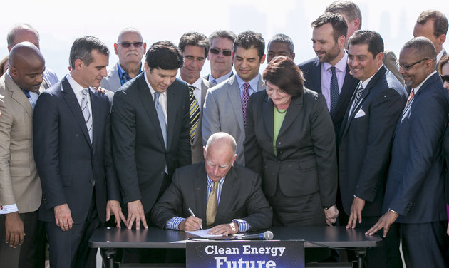 California Gov. Jerry Brown signs bill to combat climate change by increasing the state's renewable electricity use to 50 percent and doubling energy efficiency in existing buildings by 2030 at a ceremony Wednesday, Oct. 7, 2015. (AP Photo/Damian Dovarganes)