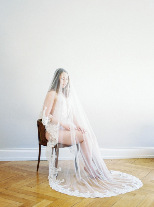 Bride sitting on a chair wearing a long lace veil.