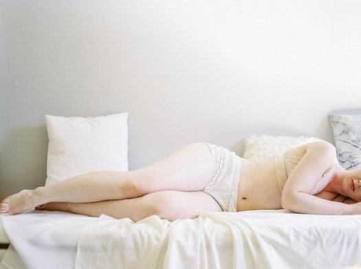 Bridal boudoir photo with bride lying down on white bed.