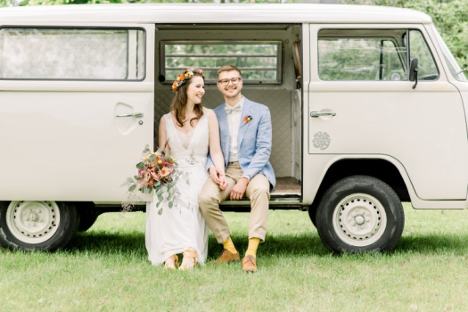 Happy newly married couple in a VW vintage minibus