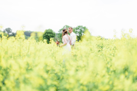 Bride and groom in a Canola field