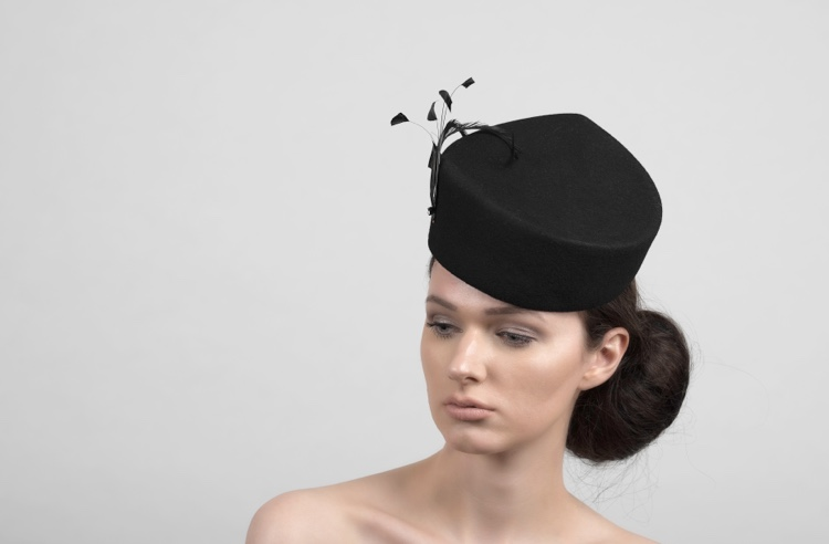 This piece is an elegant headpiece that reminds us of a British classical vintage pillbox form. The feathers add a fancy touch to this design.