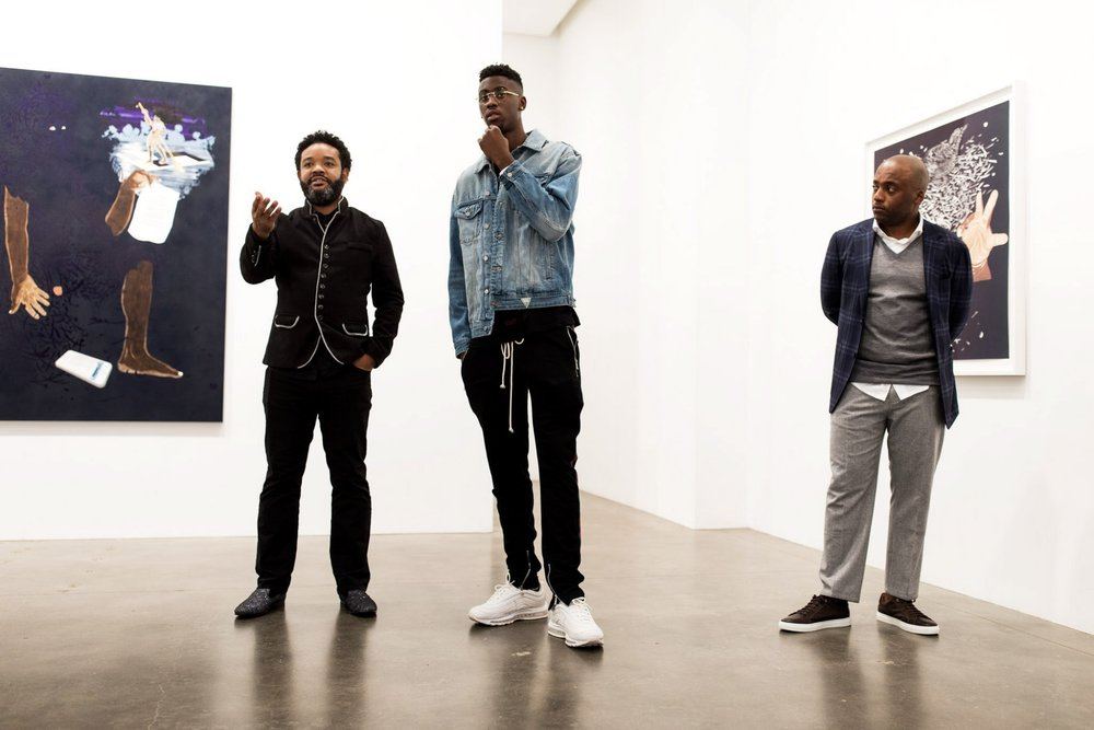 Artist William Villalongo, left, discussing one of his works of art with Caris LeVert and Gardy St. Fleur at the Susan Inglett Gallery in October. CreditDemetrius Freeman for The New York Times