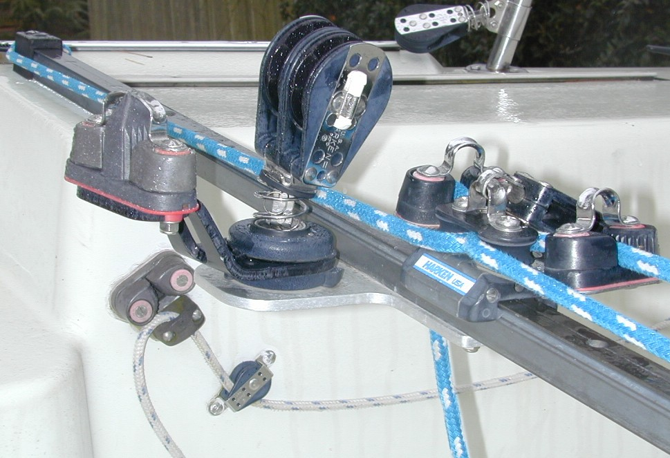 Mainsheet Barney Post Equivalent (Mounted on Traveller instead of Cockpit Floor) - Side View  Aluminum bracket bolted to Harken hi-beam traveler supports swivel mount for double ratchet main sheet block and double cam cleat for dual ratio mainsheet system from Layline. Double-ended backstay line and cleat on cockpit side beyond.