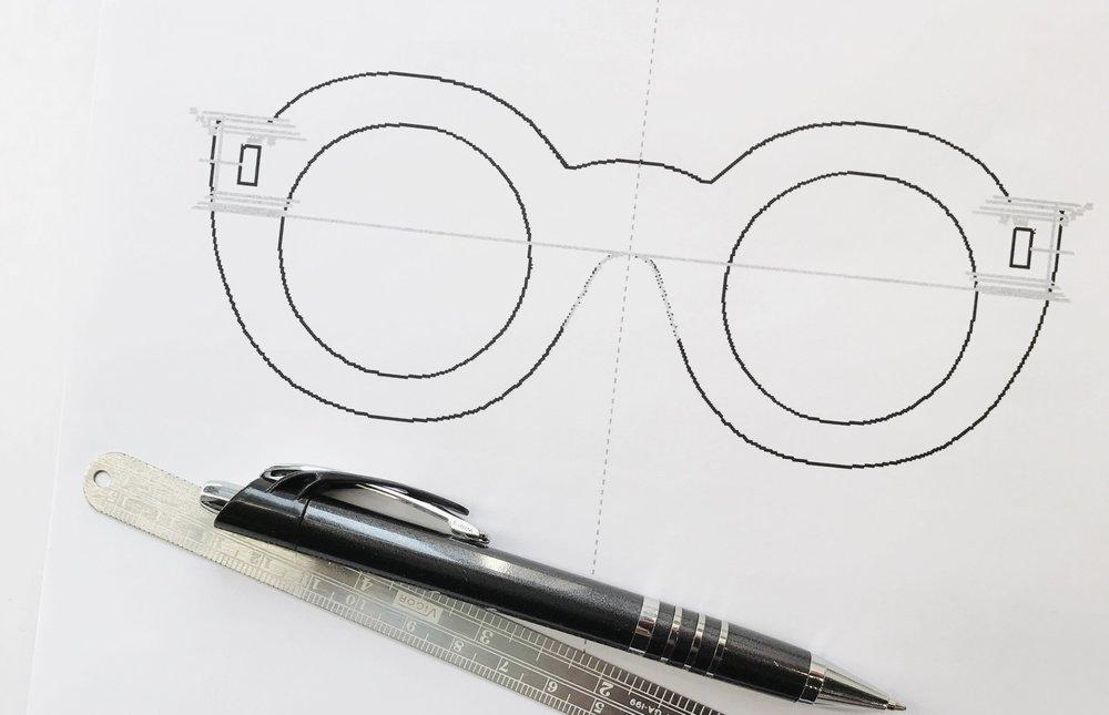 Fabrication de montures - Marie-Sophie Dion travaille à partir d'une photo de vous et un logiciel où sont intégrées une quinzaine de mesures extrêmement précises, qu'elle prend directement sur votre visage. De la taille et de la forme de l'oeil à la largeur des tempes, jusqu'à l'angle du maxillaire et la hauteur de l'oreille, rien n'est laissé au hasard. Après l'esquisse et votre approbation, la découpe assistée par ordinateur et le talent de l'artisan lunetier se mettent à l'oeuvre.