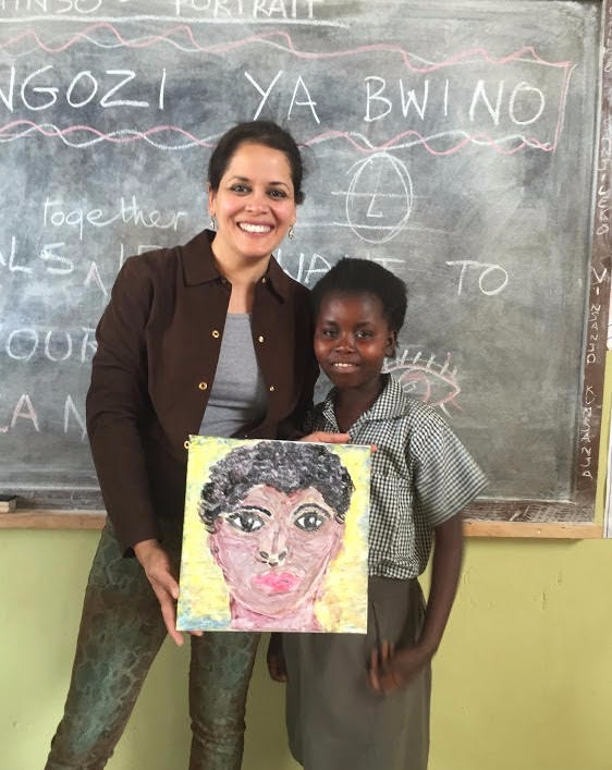 Mona '88 in the lower Zambezi doing an art project at a school in Mfuwe, holding a portrait of Tricia (right). Mona helped to fund girls' toilets and a kitchen so they would be able to stay in school post menstruation age, when most girls drop out.
