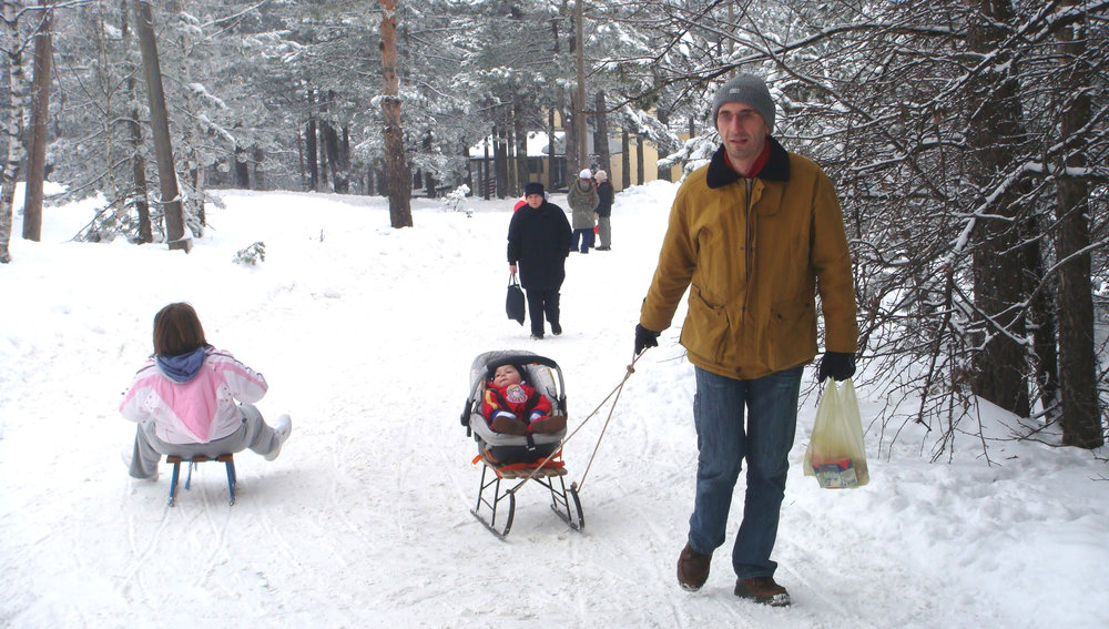 Dragan pulling Aleks in his car seat attached to a sled in Divčibare, Serbia, 2007