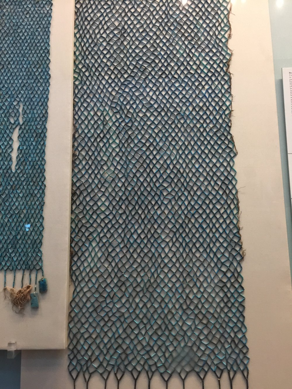 Faience bead-net belonging to the mummy Takhebkhenem. While on display, the original threads had rotted away. Conservation work included rethreading alongside surviving original thread and replacing lost beads with modern ones painted to match.
