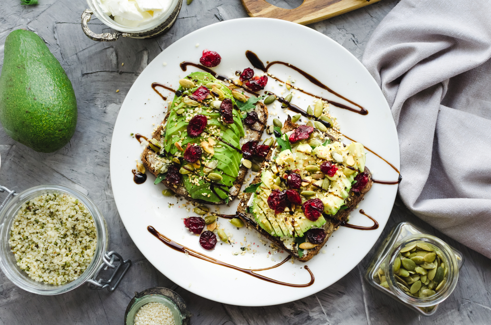 Healthy avocado toasts for breakfast or lunch with rye bread, cream cheese, arugula, sliced avocado, dried cranberry, pumpkin, hemp and sesame seeds. Vegetarian sandwiches. Clean eating..jpg