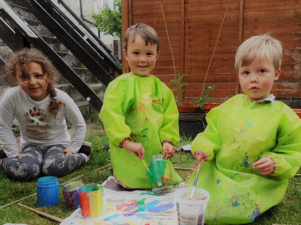 Kids painting jam jars to make garden lanterns