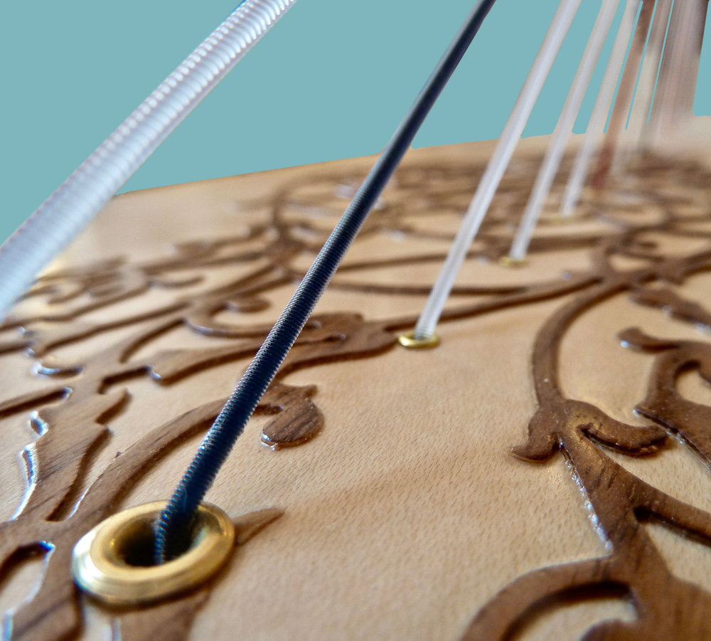 "On lever harps the bass strings exert enough force on the soundboard that it actually ""bellys-up"" a bit. This is true even in a low tension harp like the Rees Mariposa shown above."