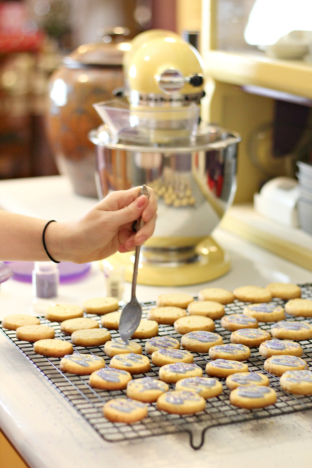 Icing the cooked and cooled shortbread cookies.