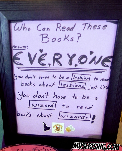 "A handwritten sign that says: ""Who can read these books? EVERYONE. You don't have to be a lesbian to read books about lesbians, just like you don't have to be a wizard to read books about wizards!"""